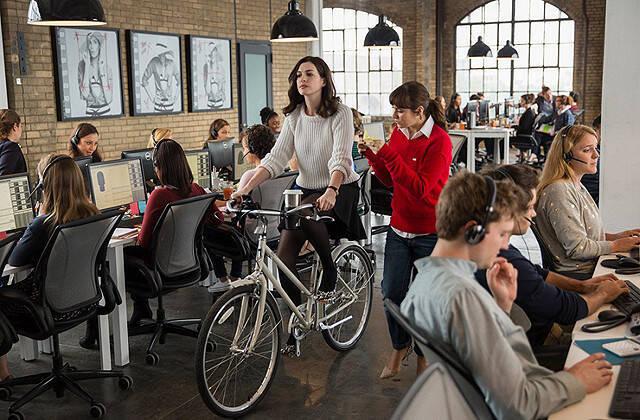 忙しさ(!?)と運動不足解消の為に社内を自転車で移動するジュールズ。周りの社員たちのファッションもキュート。(C)2015 WARNER BROS.ENTERTAINMENT INC.AND RATPAC-DUNE ENTERTAINMENT LLC ALL RIGHTS RESERVED