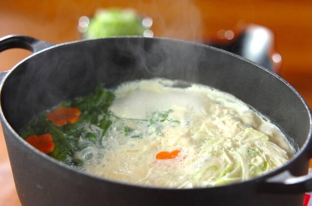 黒の鍋に入った春菊入りの豆乳鍋