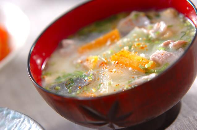 赤いお椀に入ったにんじんや豚肉のスープ