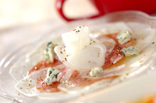 ガラスの器に薄造りのように並べられた、サラミとカブのオードブルサラダ。