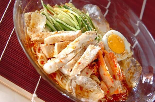 ガラスの器に盛られている、レンジ蒸し鶏冷麺