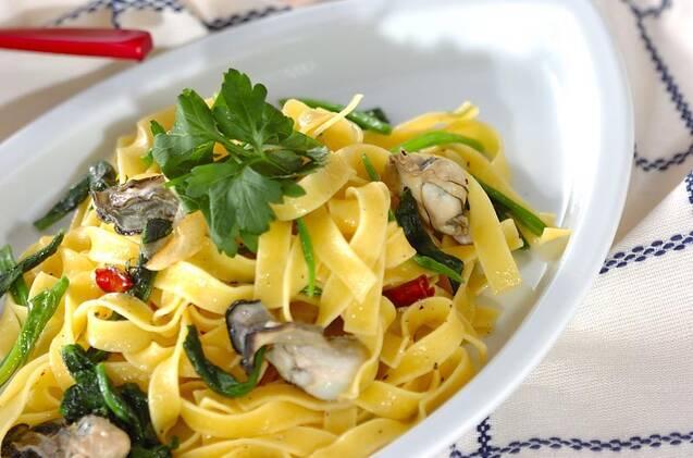 白いお皿に盛り付けられた牡蠣とほうれん草のオイルフェットチーネ