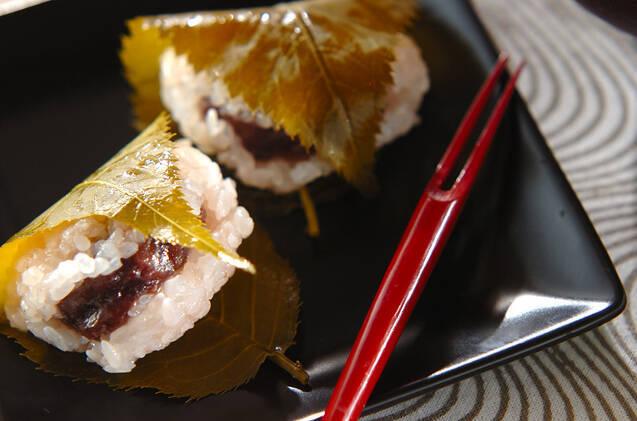 黒い四角皿に盛られた2つの桜餅と朱塗りの和菓子フォーク