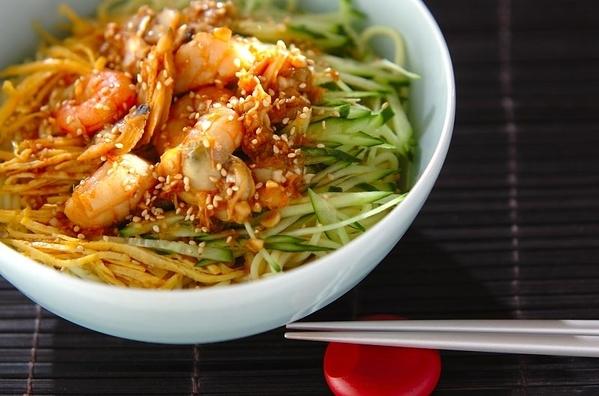 白い器に盛られている、ニンニク風味の海鮮冷麺