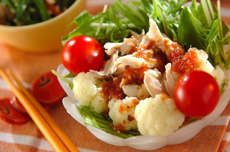 小鉢に盛られたミニトマトとカリフラワーと水菜を使ったささみの梅サラダ