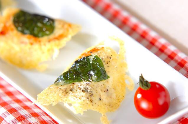 カーブのついたチーズのチュイルとミニトマトがトッピングされたお皿