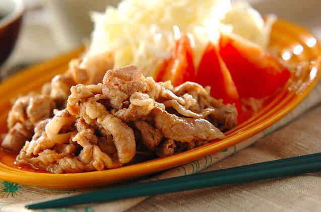 オレンジの皿に盛られた、薄切り豚ロースの生姜焼きとトマトとキャベツ