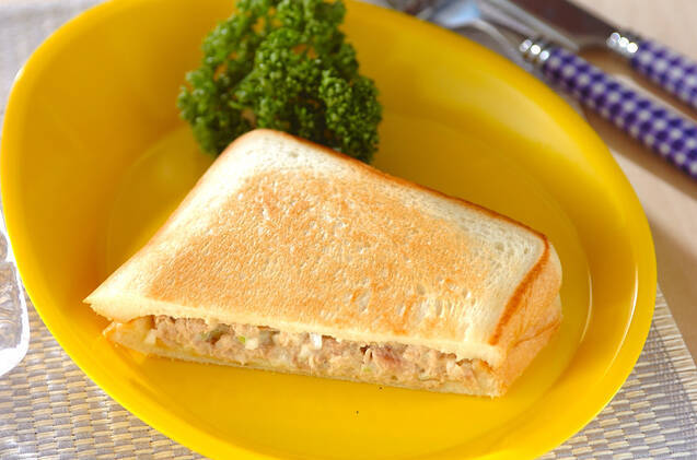 黄色い皿にのったツナマヨホットサンド半切れ