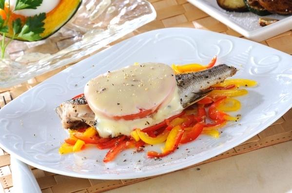 白の皿に鮮やかなピーマンとチーズのイサキ焼きが盛られている