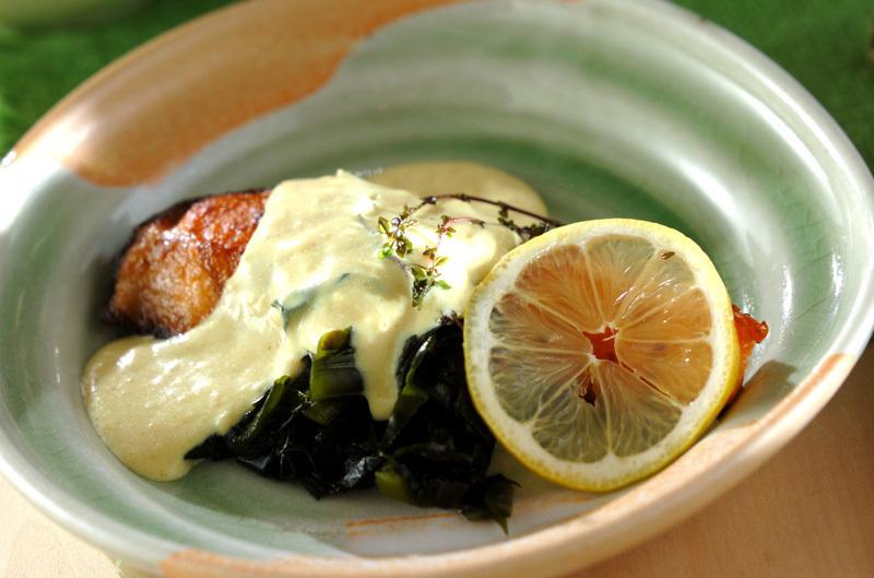 輪切りレモンとワカメが添えられたホワイトソースがけ鮭のソテー