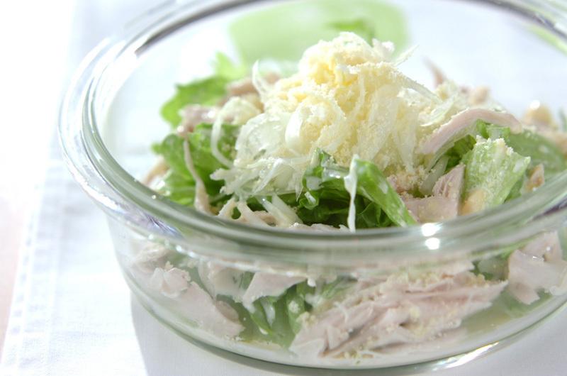 水色のランチョンマットの上にガラスの器に盛られたささみとレタスのサラダ