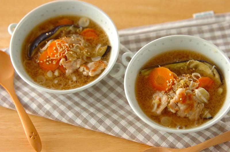 にんじんやナスが具材で、白ごまが振りかけられたスープ