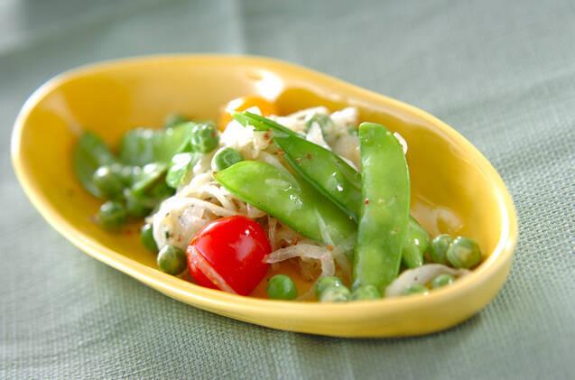 黄色の楕円型のお皿に盛り付けられたえんどう豆とキヌサヤ、ミニトマトの入ったサラダ