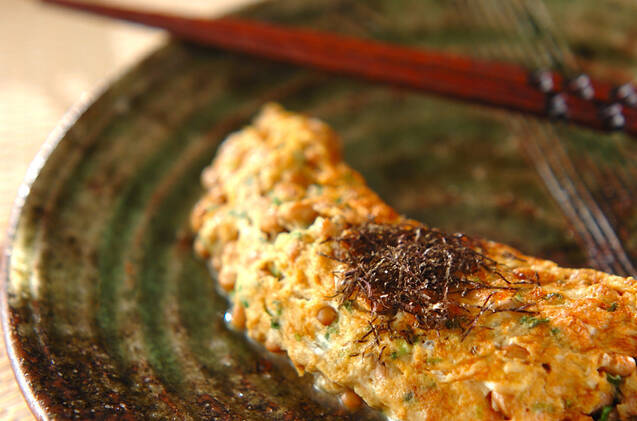 黒い皿に盛られた納豆オムレツと赤い箸