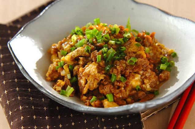 深めの角皿に盛り付けられ、刻みネギをあしらわれた豚ひき肉と卵の炒め物。