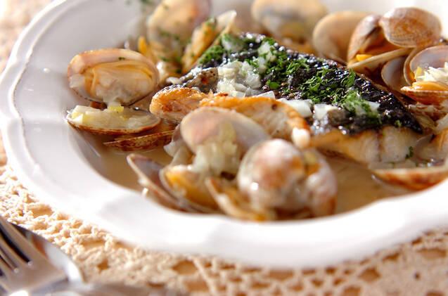 フチが波打っている白い皿に盛られた、さわらとアサリのワイン蒸し