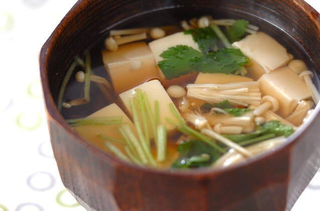 茶色のお椀に盛られた豆腐と三つ葉のお吸い物