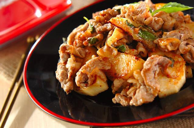 赤い縁の黒いお皿にのった豚肉と長芋のエスニック炒め