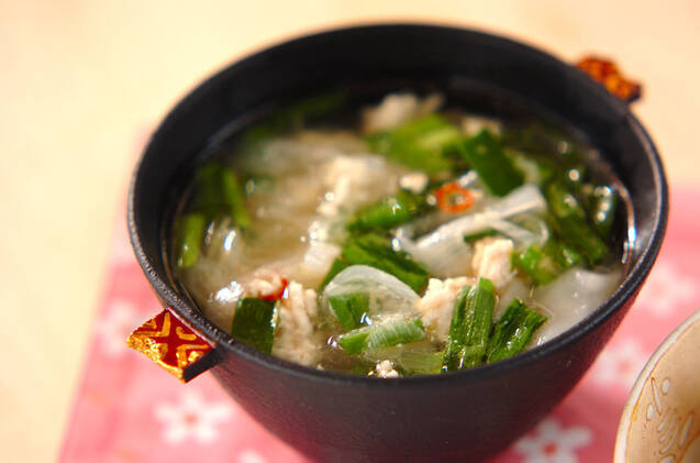 黒いお椀によそわれた鶏ひき肉やニラ、白ネギが入ったワンタンスープ