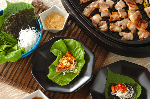 黒い鍋で焼かれている豚バラ肉と黒いお皿に盛られたサムギョプサル