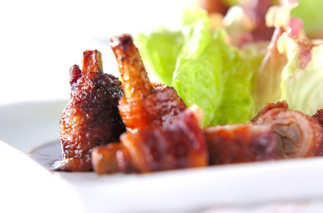 白い大皿に盛り付けられたゴボウの豚ロール焼と葉野菜