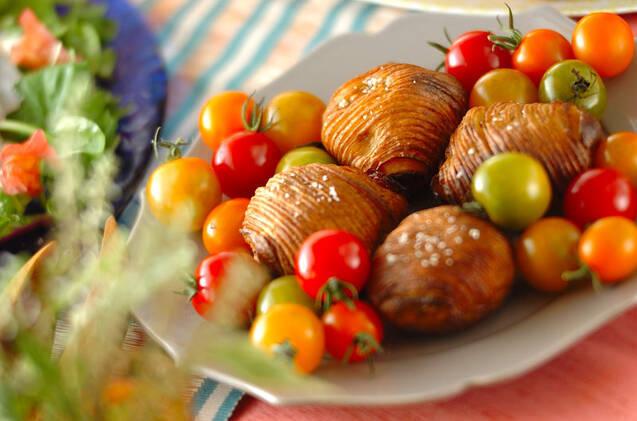 白の皿に盛られたハッセルバックポテトと色とりどりなミニトマト