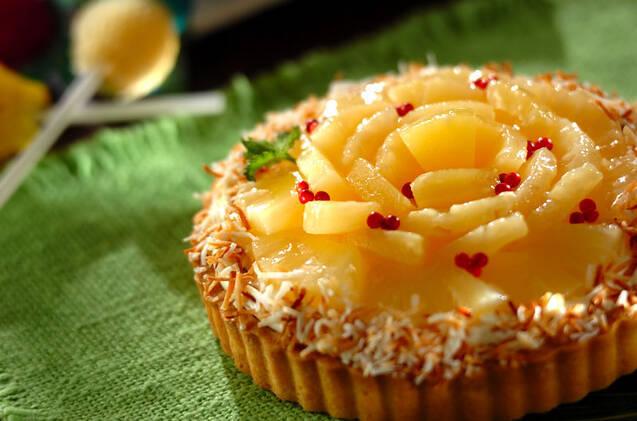 パイナップルを並べて、タルト台のフチにココナッツファインをまぶしたタルトケーキ