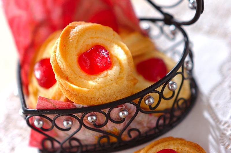 カゴに盛られた絞りクッキー数枚、中央には赤いドレンチェリーがのっている