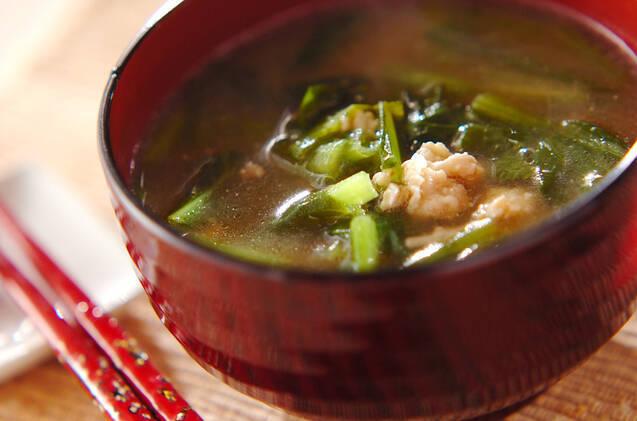 赤い茶碗に盛られた小松菜と鶏ひき肉の味噌汁