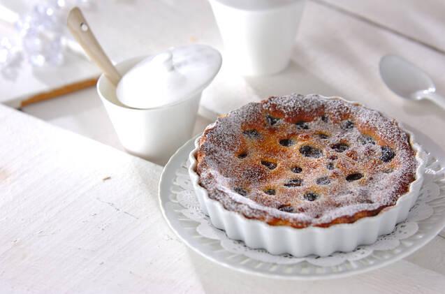 陶器のココット皿で焼かれたチェリーのクラフティのわきに、ポットとスプーンが並んでいる。