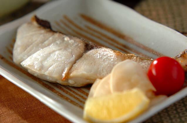 鯛の切り身を塩焼きにして平皿にトマト、レモンと一緒に盛りつけた画像