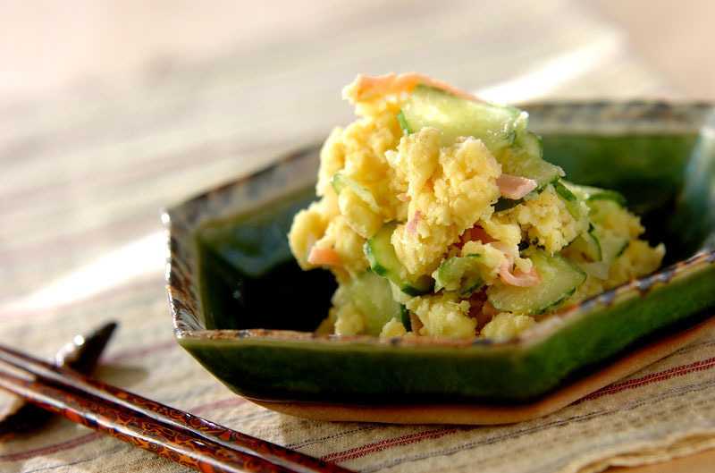 緑の皿に盛られたさつまいもとキュウリが入ったサラダ