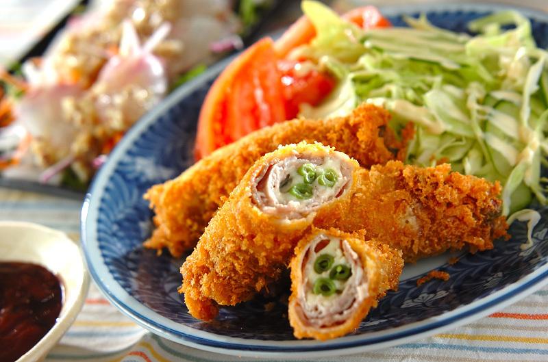 青いお皿に盛り付けられた豚肉のチーズロールカツ
