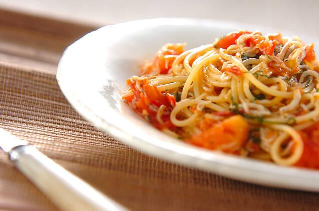 白い皿に盛られた、しらすとトマトのパスタ