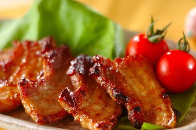 白っぽい皿に盛られている、豚バラ肉のソテーと野菜