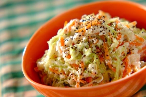 オレンジ色の器に入ったにんじんとキャベツの白和え風サラダ
