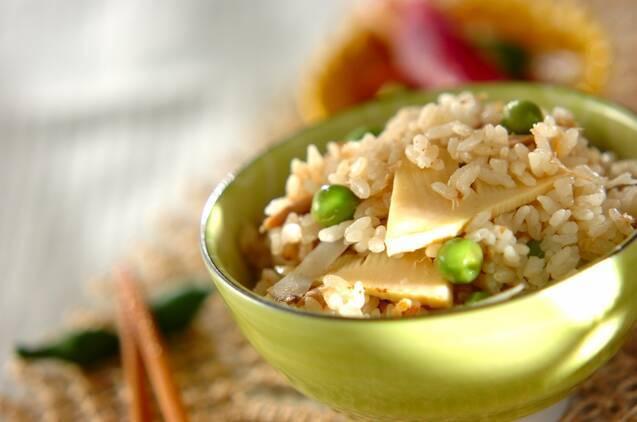 黄緑色のご飯茶椀によそられたグリーンピースとツナと野菜の炊き込みご飯