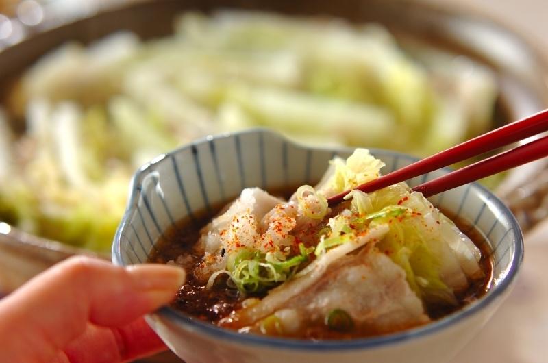 小皿にとった豚バラと白菜の鍋を箸でとる