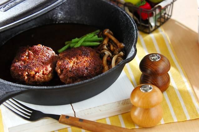 スキレットに入ったふたつのハンバーグと、添えられたフォークと調味料