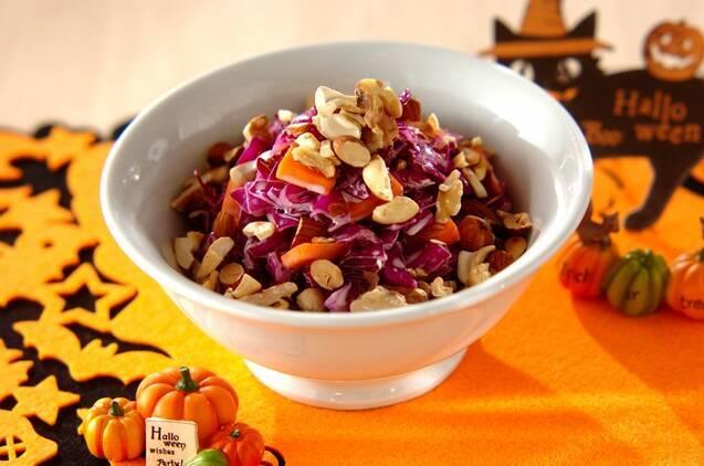 ミックスナッツを散らした紫キャベツとニンジンのサラダが入った白いボウル