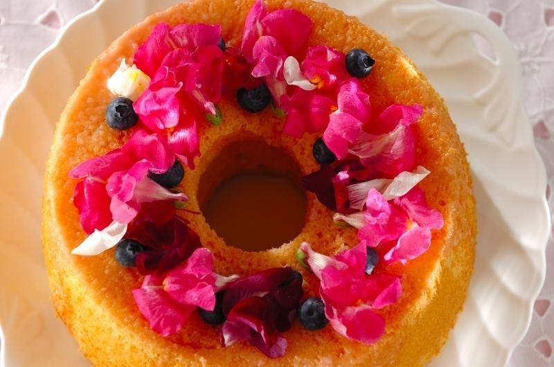 シフォンケーキの上にピンクや赤のエディブルフラワーをのせたケーキ