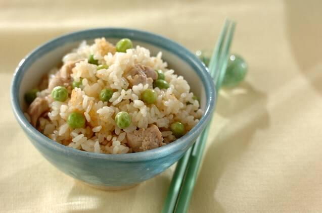 翡翠色のご飯茶椀によそられた鶏とグリーンピースの混ぜご飯