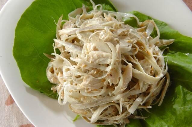 白い皿に敷かれた葉っぱの上に盛られた鶏肉とゴボウのサラダ