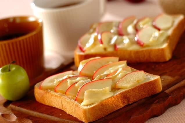 リンゴとカマンベールチーズを交互に並べたチーズトーストをのせた木製トレー