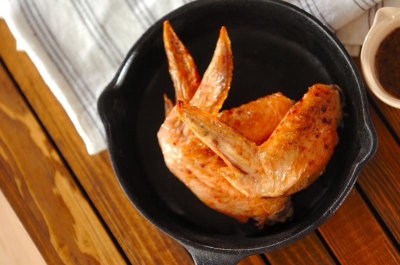 鉄製のグリルパンの中にある鶏手羽料理