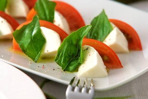 白い皿に盛られたトマト、バジリコ、モッツァレラのサラダ