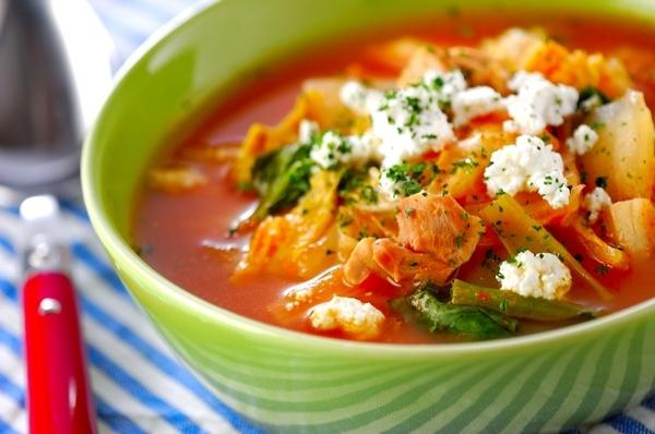 緑の皿にトマトスープと野菜、チーズが入っている
