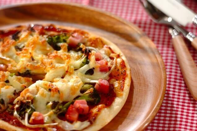 角切りのベーコンとブロッコリーをのせた薄いピザ生地