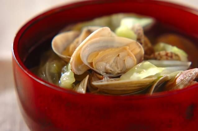 朱の椀に盛られた、あさりとキャベツのスープ