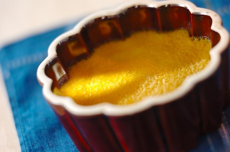 赤い陶器のカップ入りココナッツカボチャプリン
